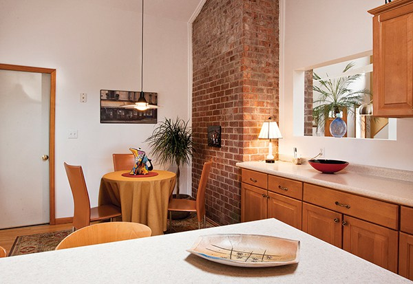 The Exposed Brick Chimney In The Kitchen Is Offset By Clean Modern