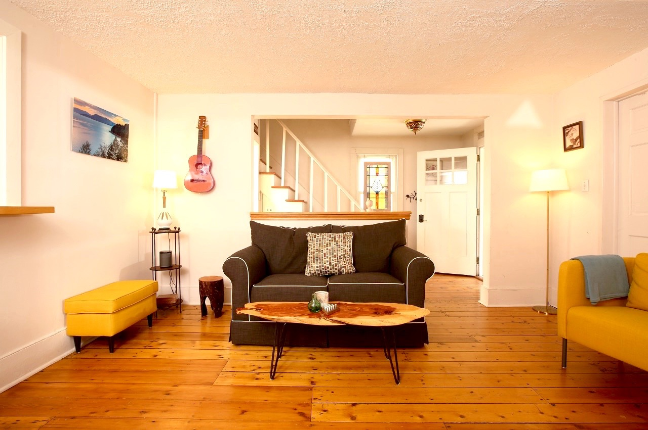 The warm-hued wood floors are a star of the living room in this charming house in High Falls
