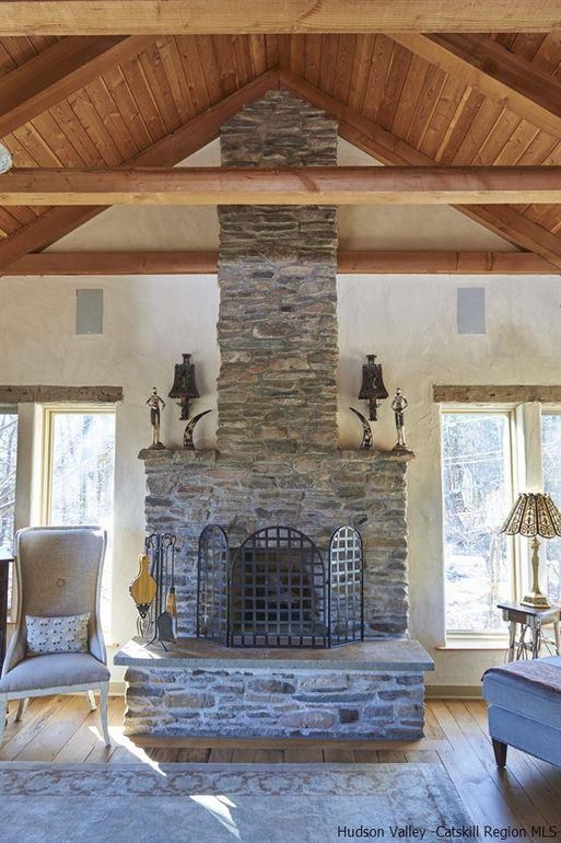 Stone fireplace in the master bedroom of this romantic Woodstock home