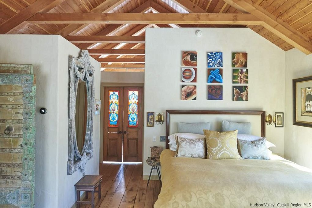 Master bedroom with stained glass and vaulted ceiling in this romantic Woodstock home